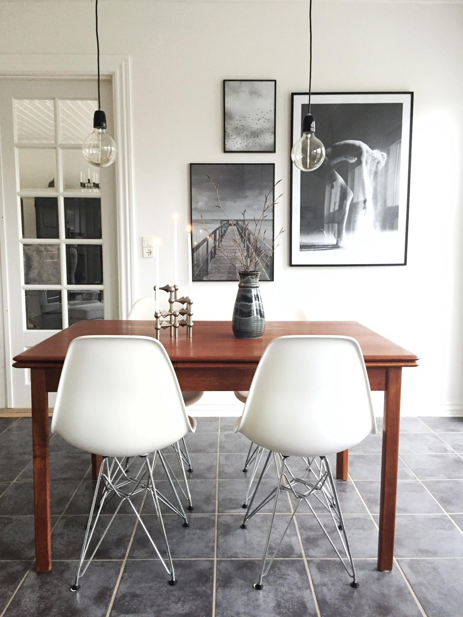 Spisestue med hvid væg og billeder